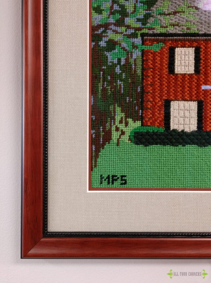 detail of framed needlepoint framed in wood